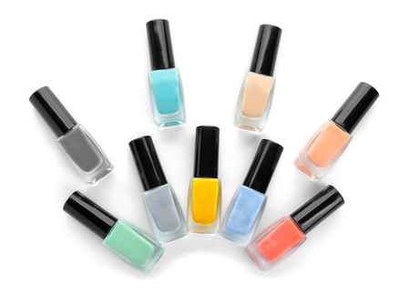 Bottles of colorful nail polish on white background, flat lay Фото со стока