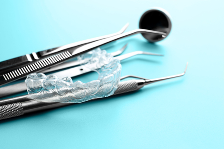 Dental instruments and occlusal splint on color background, closeup