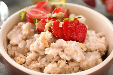 Tasty oatmeal with strawberries in casserole, closeup