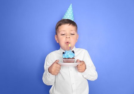 Little boy blowing out candle on birthday cupcake against color background