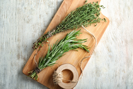 Board with fresh herbs and thread on wooden background