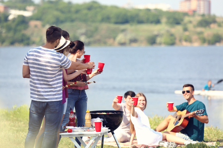 Young people having barbecue party on sunny day outdoors Stock Photo