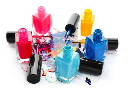 Open bottles of nail polish on white background