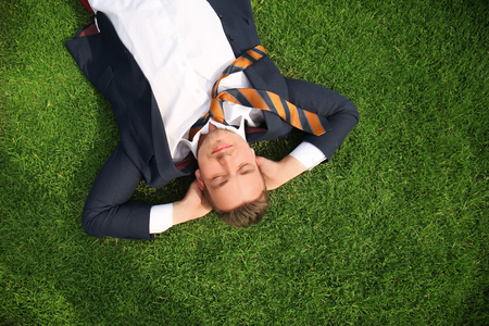 Young man in formal clothes relaxing on green grass outdoors