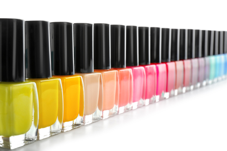Bottles of colorful nail polish on white background