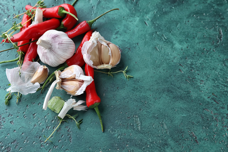 Fresh garlic, thyme and chili peppers on color textured background Imagens