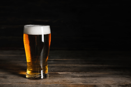 Glasses with cold beer on wooden table against dark background