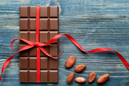 Tasty milk chocolate bar with ribbon and cocoa beans on wooden background