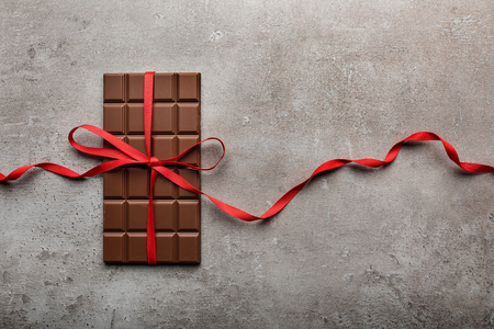 Leckere Milchschokolade mit Band auf grauem Hintergrund Standard-Bild