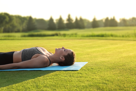 Beautiful young woman lying on yoga mat outdoors in the morning