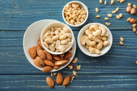 Bowls with different nuts on wooden background