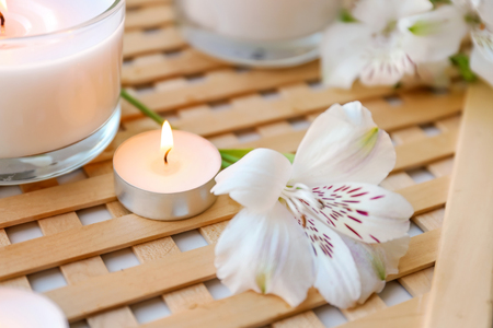Burning wax candles with flower on table
