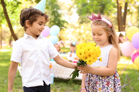 Little girl receiving flowers from cute boy at birthday party outdoors Archivio Fotografico
