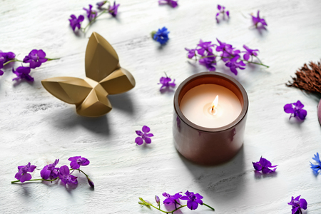 Burning candle and beautiful flowers on white wooden table 写真素材 - 113592269