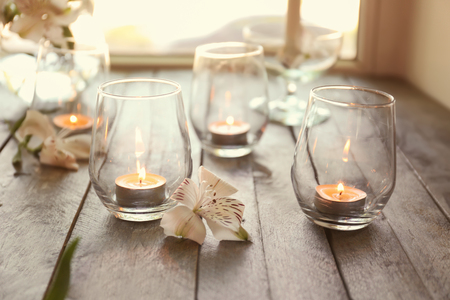 Beautiful burning candles in glasses on wooden windowsill Stock Photo