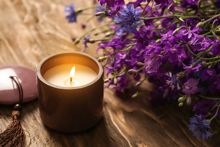 Burning candle and beautiful flowers on wooden table