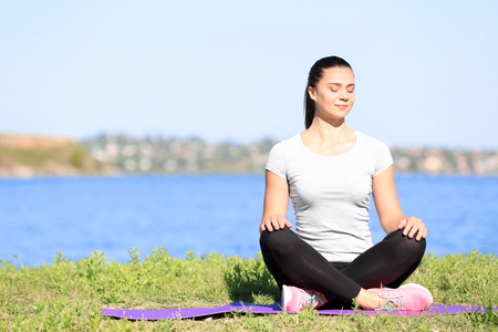 Sporty young woman practicing yoga outdoors