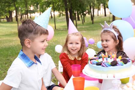 Cute children celebrating birthday outdoors