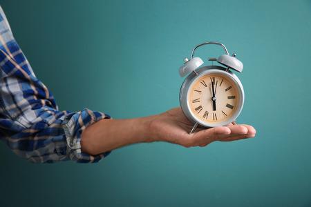 Man holding alarm clock on color background. Time management concept