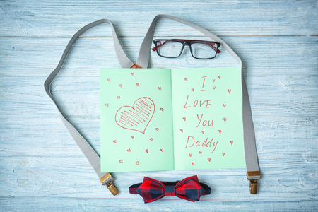 Composition with card for Father's Day on wooden background
