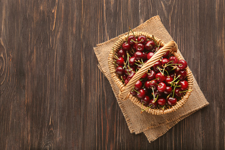 Wicker basket with tasty cherries on wooden table