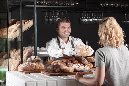 Woman buying fresh bread from cheerful baker in shop