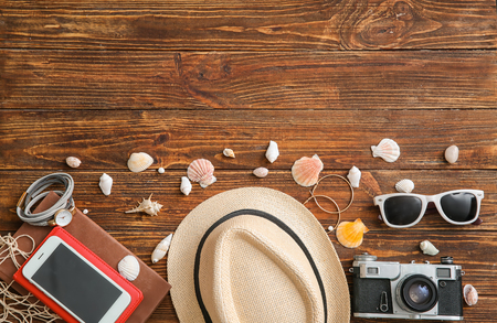 Composition with photo camera, mobile phone, seashells and accessories on wooden background