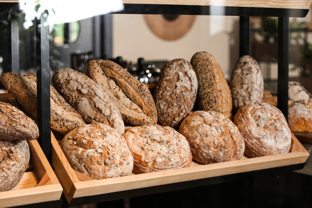 Counter with assorted fresh bread in bakery Stock Photo