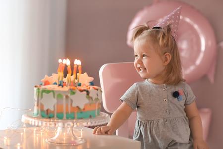 Jolie petite fille avec un gâteau d'anniversaire assis sur une chaise dans la chambre Banque d'images