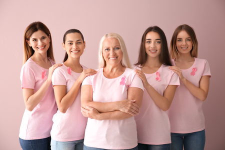 Beautiful women of different ages with pink ribbons on color background. Breast cancer concept