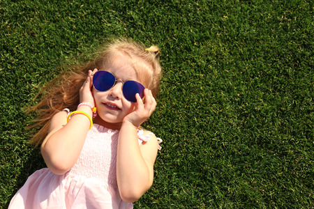 Cute little girl relaxing in park on sunny day