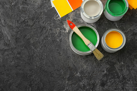 Cans of paint and brush on grey background