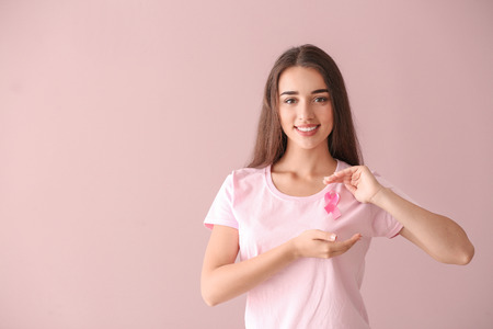 Beautiful woman with pink ribbon on color background. Breast cancer concept