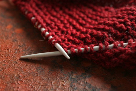 Knitting needles with unfinished clothes on table, closeup