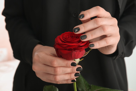 Young woman with beautiful manicure holding red rose, closeup