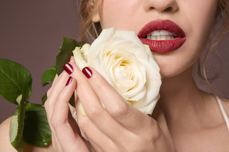 Fashionable young woman with beautiful manicure and rose on color background, closeup