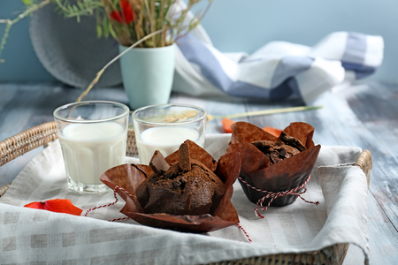 Tasty chocolate muffins and glasses of milk on table