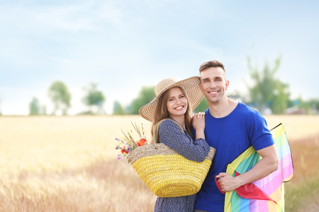 Happy young couple with kite in a field Imagens