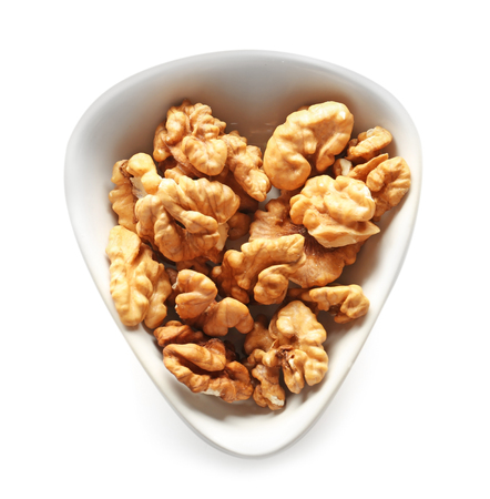 Bowl with tasty walnuts on white background