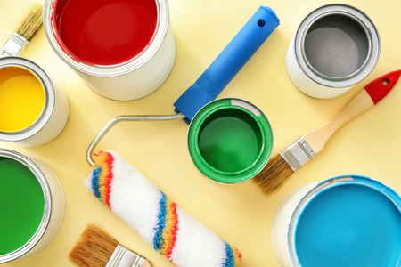 Paint cans with roller and brushes on color background