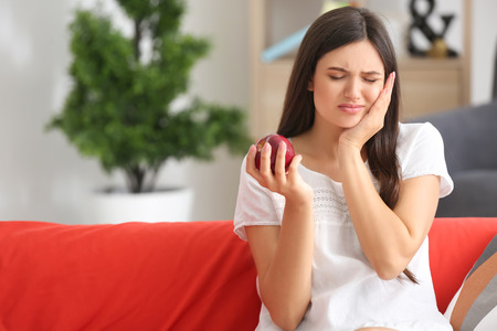 Young woman with sensitive teeth and apple on sofa at home