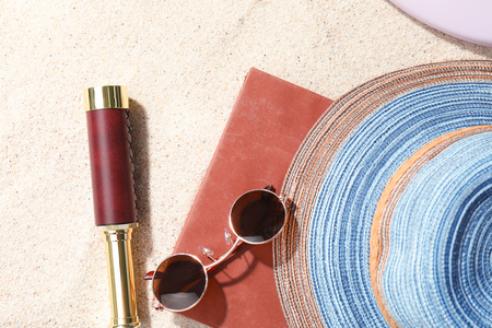 Composition with spyglass, book and female accessories on beach sand