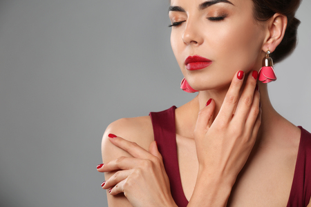 Young woman with beautiful manicure on grey background