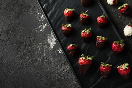 Piatto con deliziosa fragola ricoperta di cioccolato su sfondo grigio strutturato