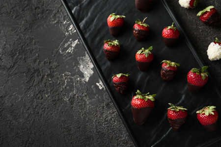 Plate with delicious strawberry covered with chocolate on grey textured background 스톡 콘텐츠