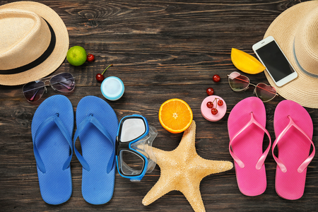 Composition with beach accessories and smartphone on wooden background