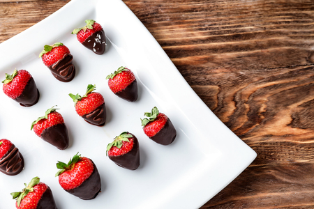 Strawberries covered with chocolate on plate