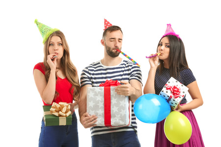 Young people in birthday party caps with gift boxes on white background