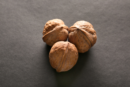 Unpeeled walnuts on dark background