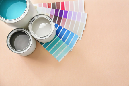 Paint cans with color palette samples on light background